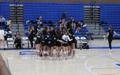 Varsity girls having a motivational team huddle.