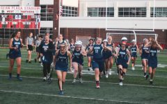 Girls Lacrosse team storming the sidelines after winning their first game.