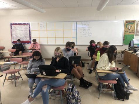 A group of students work in a classroom with their faces covered. While this was common in 2020, it is no longer a school requirement.